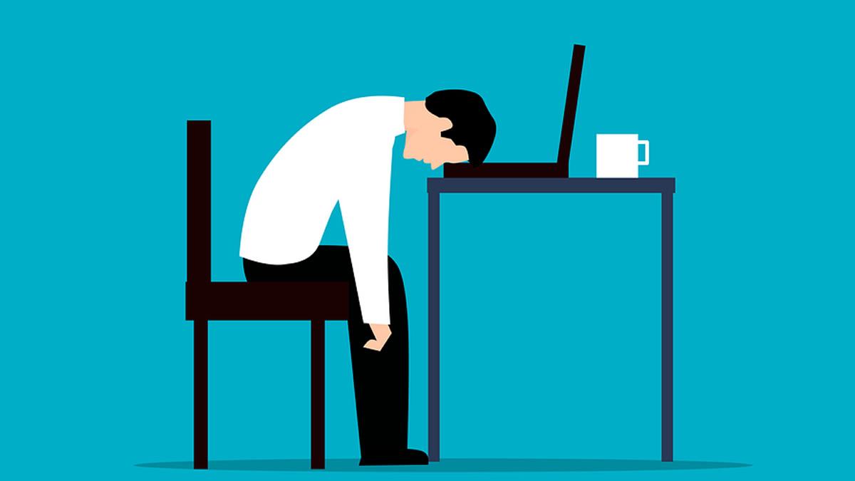 疲れ切ってパソコンに頭を埋める人
